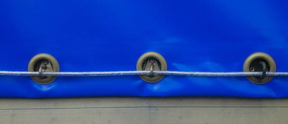 Blue tarps secured using grommets