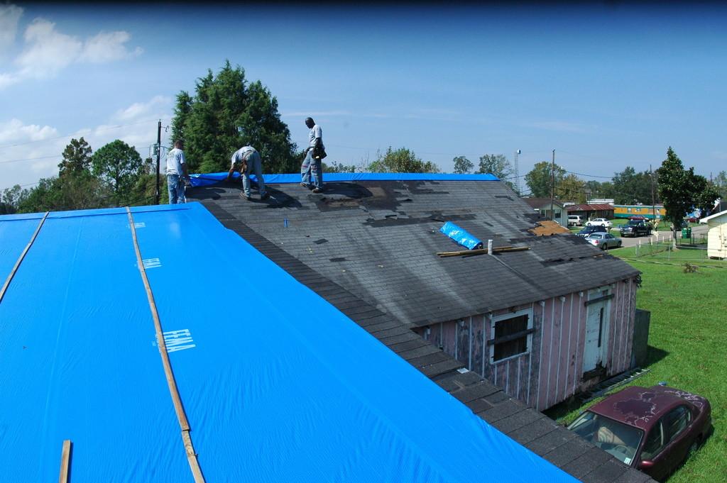 Installing roof tarps during renovation.
